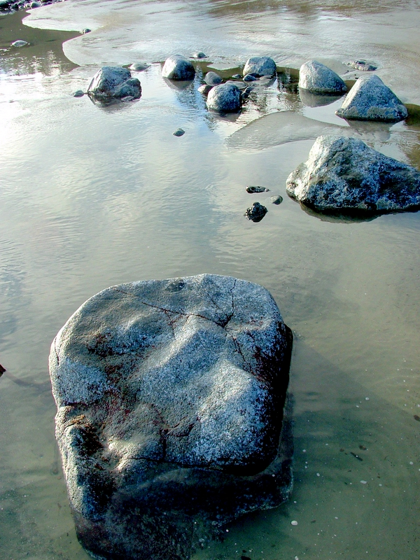A rock in the water at the beach.